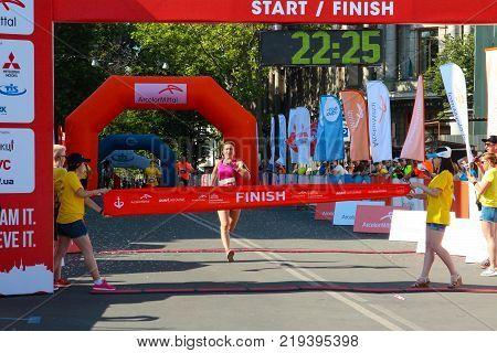ODESSA UKRAINE - 25 JUN 2017: Excited female runner crossing the finshline of a marathon. Marathon winner woman at finish. Happy marathon runner finish line.