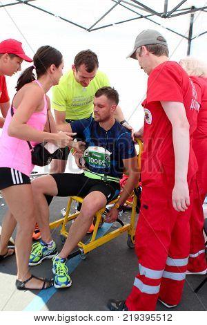 ODESSA UKRAINE - 25 JUN 2017: Runner receives medical attention. Paramedic helping male runner wihh accident.