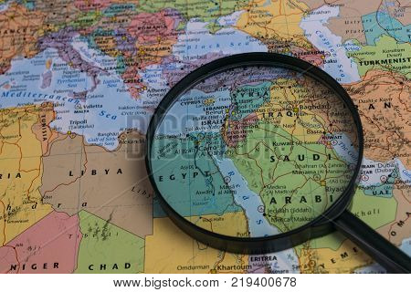Middle East map through magnifying glass on a world map