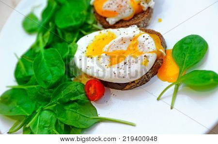 Delicious eggs Benedict on the sandwich with spinach and cherry tomato on the white plate, tasty organic nutrition, healthy food concept