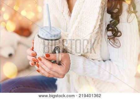A girl in a white sweater and scarf holds a cup of hot drink in her hands.