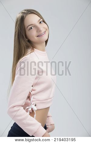 Dental Concepts. Portrait of Happy Teenage Female With Teeth Brackets. Posing with Smile Against White.Vertical Shot