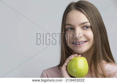 Dental Concepts. Portrait of Happy Teenage Female With Teeth Brackets. Posing With Green Apple and Smiling Against White.Horizontal Shot