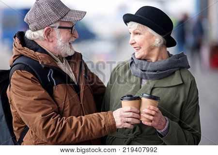 Cheers. Profile of optimistic happy senior couple are standing together outdoors while clinking cups of coffee and looking at each other with smile. They are feeling gladness and pleasure