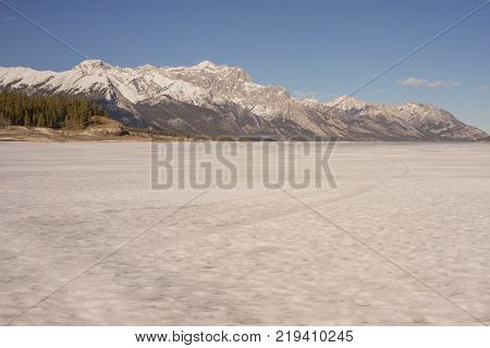 Icy landscape of Abraham Lake with mountains in the background.