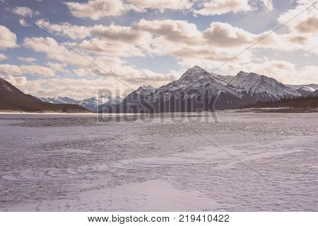 Mountain and frozen Abraham Lake Winter Landscape.