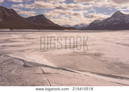 Winter landscape of Abraham Lake with mountains in the background.