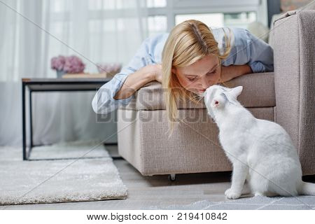 Quite girl lying on daybed and kissing domestic cat. Animal is sitting on floor
