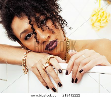 young afro-american girl laying in bath with foam, wearing swag jewelry flawless, making selfie, modern lifestyle concept, rich woman