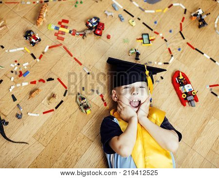 little cute preschooler boy among toys at home in graduate hat smiling posing emotional, lifestyle people concept, wooden floor close up