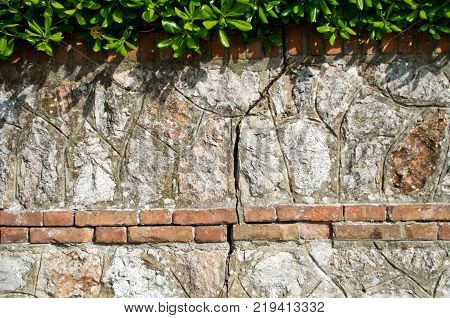 stone wall with brick lines and periocolose vertical crack