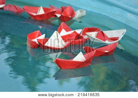 Red and white paper ship in water
