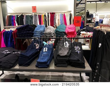 RISHON LE ZION, ISRAEL- DECEMBER 17, 2017: Modern clothes in a shop on a hanger. Shirts and sweaters of different colors and denim for youth. Clothes of different styles on the hanger in the showroom.