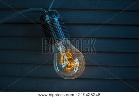 The old glass bulb burns dull orange light on a gray wooden background