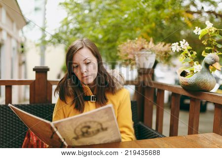 Beautiful Happy Caucasian Young Smiling Brown-hair Woman In Yellow Coat Reading, Ordering From Menu
