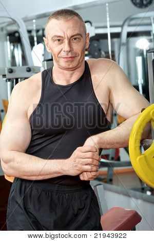 Mature sporty man in the gym centre.