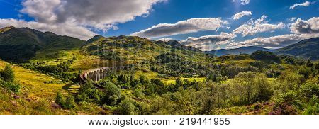 Summer panorama of Glenfinnan Railway Viaduct in Scotland and surrounding mountains