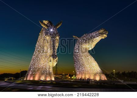 FALKIRK, UNITED KINGDOM - SEPTEMBER 7, 2015 : The Kelpies Horse statue lit up at night at The Helix Park in Falkirk, Scotland