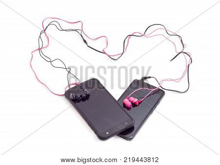 Two pair of red and black earphones connected to smartphones wires of earphones are laid out in the shape of a heart on a white background