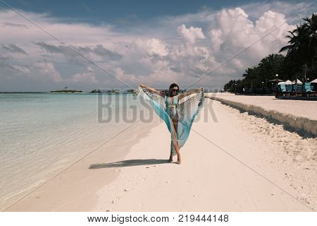 Woman In Elegant Beach Clothes Relaxing On Maldives Island