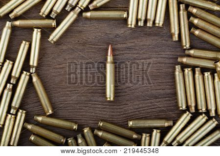 Rifle bullets on wood table with low key scene. Close-up photo. High resolution photo.