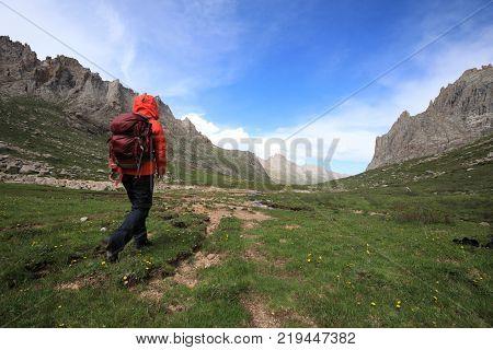 female adventurer walking on high altitude mountain