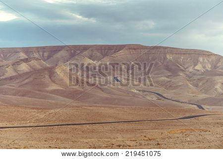Landscape view on desert road in judean negev desert in Israel. Dry summer sunny empty valley with sand, mountains, rocks and stones. Horizon sky and clouds