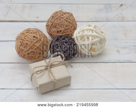 A present or gift box wrapped by rough brown recycled paper and tied with brown hemp rope as ribbon with clear and glitter silver ornamental balls on white rough wooden background