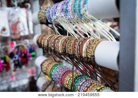 Braided leather bracelets with beads in the store. photo on the open diaphragm.