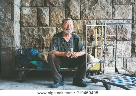 Homeless. Happy and smilling homeless man sittinh in the shadow of the building on the urbyn street in the city