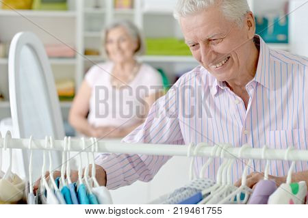 Portrait of senior couple choosing clothes in shop