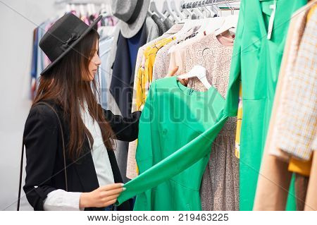 Beautiful young woman examinign a dress while shopping at the local boutique fashion glamour style beauty clothing mall consumerism retail sale discount consumerism customer buyer shopper lifestyle.