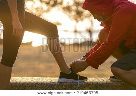 Runners couple tying running shoes to run banner. Trainer lacing woman's shoes laces for jogging motivation at park. Healthy lifestyle Concept.