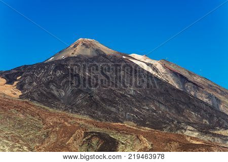 An uphill view of the colourful Teide volcano in Teide National Park, Tenerife, Canary Islands. Pictured in the distance is a cablecar leading up to the 3718 m Teide peak, the tallest peak in Spain.