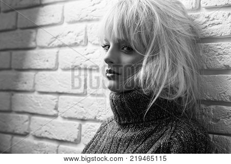 Monochome portrait of a ebautiful young mysterious woman looking to the camera playfully leaning on the wall copyspace seduction temptation sexuality beauty.