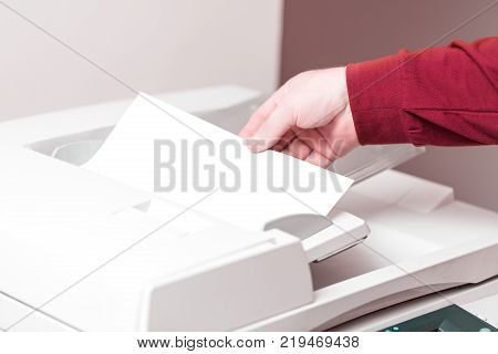 Man putting paper sheet on printer feed for scanning. Office work concept