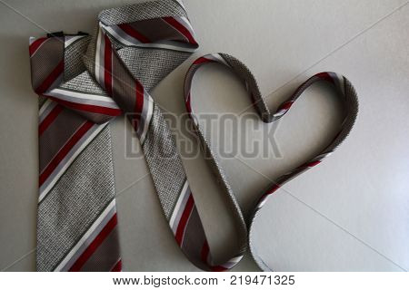 mens striped tie folded in the shape of a heart