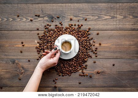 Hand hold cup of milky coffee on dark wooden table top view. Coffee background