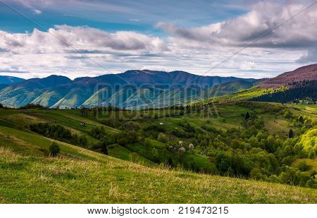 beautiful mountainous countryside in springtime. village outskirts with rural fields on rolling hills.
