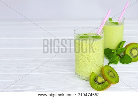 Kiwi smoothies and kiwi fruit for breakfast in the morning on white a wooden floor.