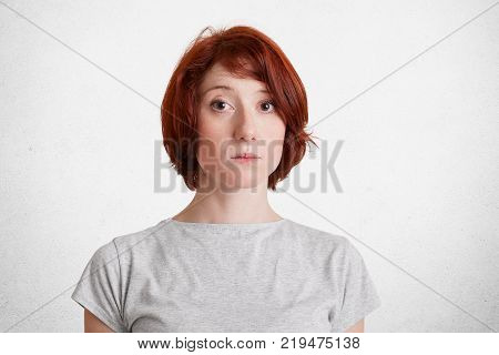 Portrait Of Serious Redhead Woman Wears Casual T Shirt Listens Attentively Interlocutor, Tries Under