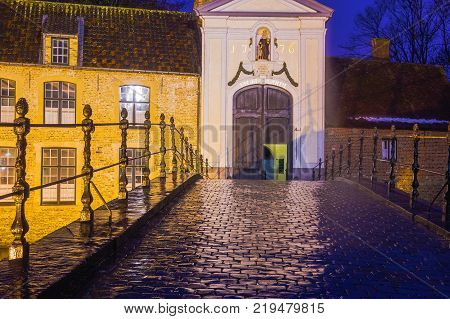 Bruges, Belgium - December 13, 2017: The Beguinage along a canal across from Minnewater Park in the historic town of Bruges, a UNESCO World Heritage site in Belgium in West Flanders.