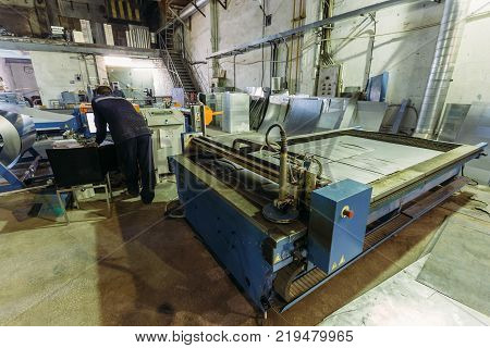 Operator works with plasma cutting machine with program control  in metalwork factory.