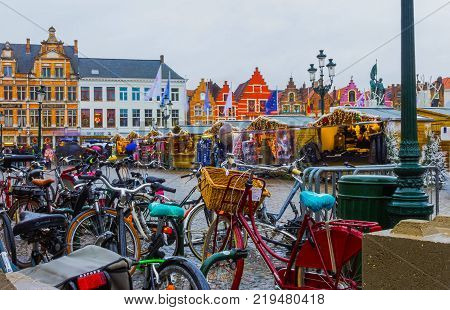 Bruges, Belgium - December 13, 2017: The people going at Market Square at Bruges, Belgium on December 13, 2017