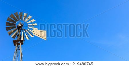 Multi-bladed windpump on blue sky background. Text for space