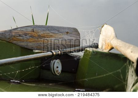 Old wooden oars and a fishing rod lie in a boat. On the oars there is a cobweb. Dewdrops hang on the fishing line. Background. Theme of fishing.