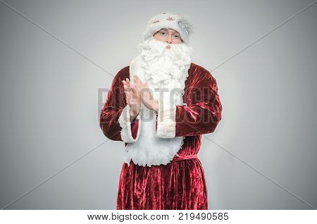 Santa Claus applauds isolated on gray background.