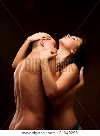 A loving couple embraces on brown background