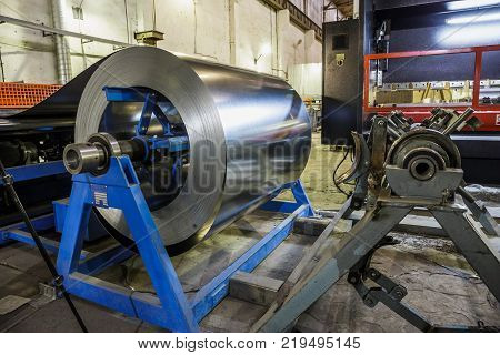 Roll of steel sheet and machinery tools for manufacturing metal pipes and tubes for industrial ventilation systems in the factory workshop, toned