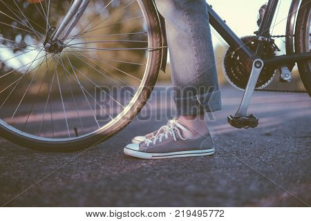 Beautiful Young Woman Riding Pink Bicycle In Green Park. Legs Of A Woman In Sneakers With A Bicycle